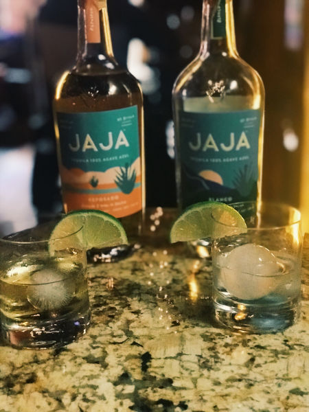 Jaja tequila on round ice cubes with lime